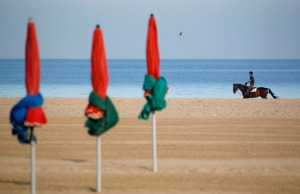 A man rides his horse at a beach in Deauville